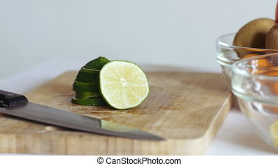 Woman's hands puts lime pyramid in glass plate. Healthly concept