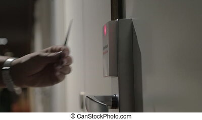Woman opening hotel door with a cardkey - Close-up shot of a...