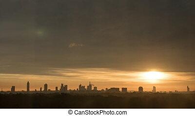 Timelapse of sun rising in overcast sky over the city -...