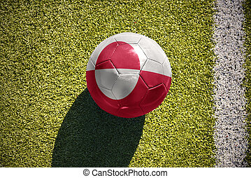 football ball with the national flag of greenland lies on...