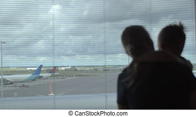Child and mother looking at airplanes through window - Son...