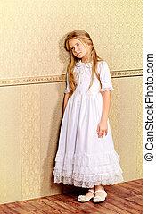 sad little girl - Sad little girl in a white dress leaning...