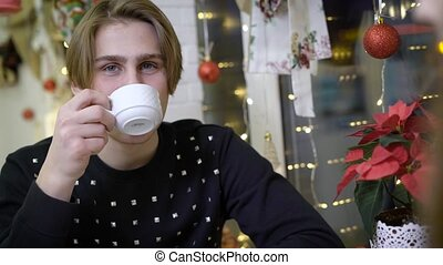 Portrait of attractive young guy, he is sitting in the cafe...