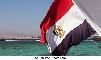 Egyptian flag flies in the wind against scenic beautiful Red...