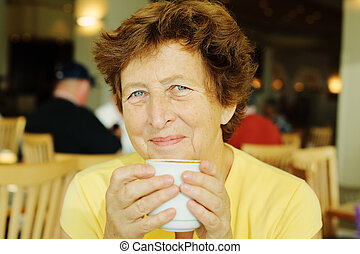 Portrait of beautiful 70 years old woman drinking morning...