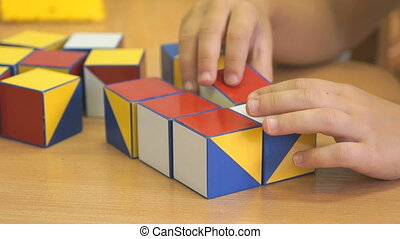 Little girl collecting pattern using colored cubes - Little...