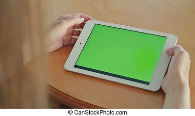 Woman looking at tablet computer with green screen in cafe -...