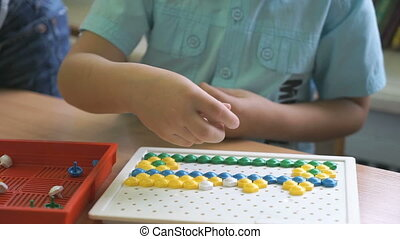 Little boy collecting pattern using colored chips - Little...