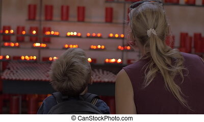 Mother and child looking at candles in church - Mother and...