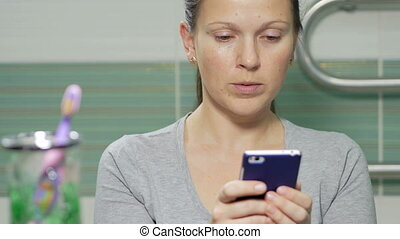 Young attractive woman on the phone dials sms in the bathroom. She smiles, and both hands are concentrated respond to a message