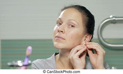Young attractive woman removes the earrings in the bathroom...