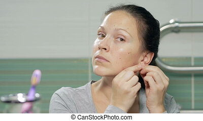 Young attractive woman wears pearl earrings in the bathroom...
