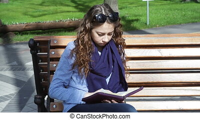 young woman sits on a bench in the Park and reading book