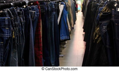 View of Racks with Colorful Men Shirts in Shop - closeup...