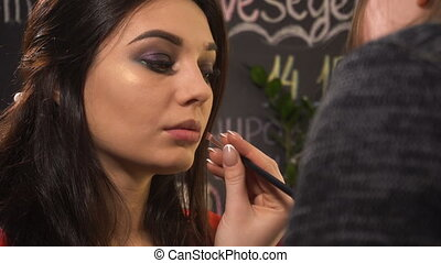 Makeup artist makes makeup for woman model in beauty salon....