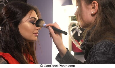 Makeup artist makes makeup for woman model in beauty salon