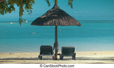 Summer vacation on the coast in tropics - Two empty chaise...