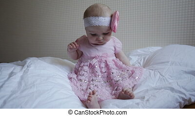 little girl in a pink dress sits on the bed
