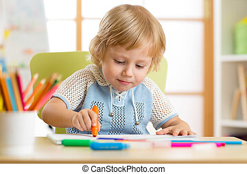 Cute little boy is drawing with felt-tip pen in preschool