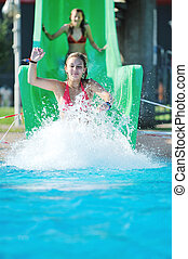 girl have fun on water slide at outdoor swimming pool -...