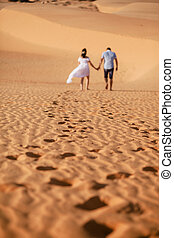 couple travel sand dune. out of focus