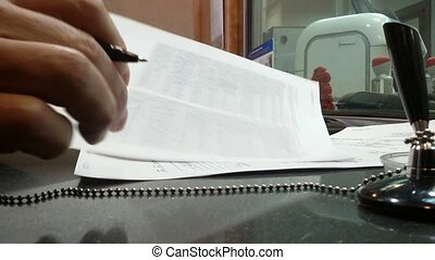 Close-up of a man in a bank signs a contract.