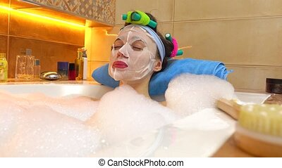 Beautiful young woman wearing cosmetic face mask relaxes in...