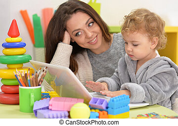 mother and daughter using laptop, parts of constructor are...