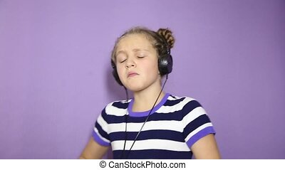 young girl with pigtails listening music on headphones and...