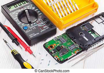 repair and testing smartphone with a multimeter on a white...
