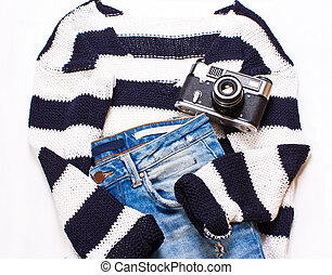 Women's clothing, sweater, jeans and a camera on a white...