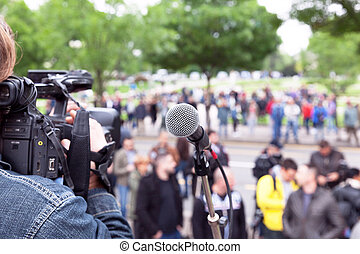 Microphone in focus, cameraman filming blurred crowd -...