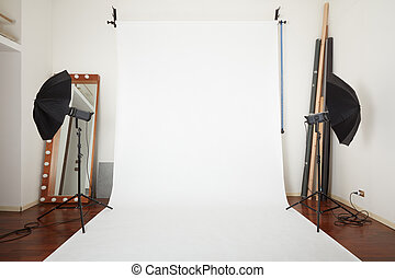 Photographic studio interior with white blank paper background