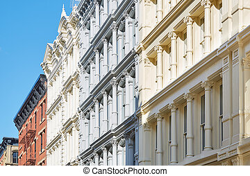 Ancient houses facades in New York, blue sky in Soho -...
