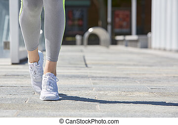 Woman with sport shoes and tracksuit in the city in summer