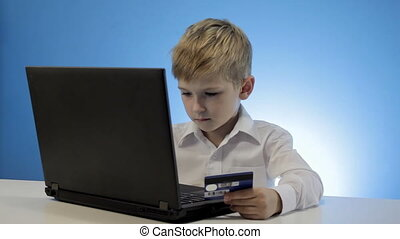 Cute little boy use laptop and credit card