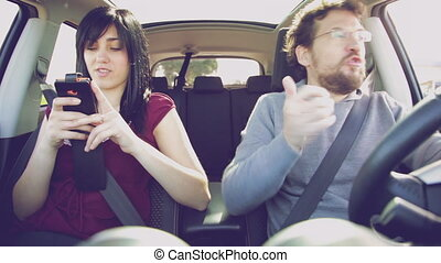Man in car with girlfriend angry with cell phone addiction -...