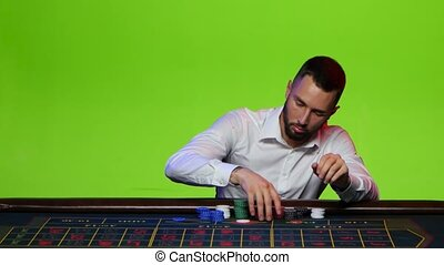 Man intently lays out all their chips won - Man dressed in a...
