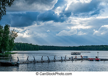 Calm heavenly landscape with thick clouds over the forest lake, quiet place to relax