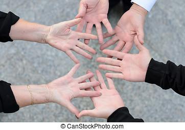 Overhead view of three friends and their hands in a circle...
