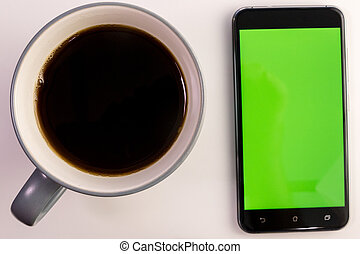 Smart phone with green screen next to coffee cup - Smart...