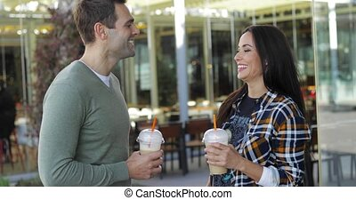 Young couple drinking takeaway beverages standing side by...