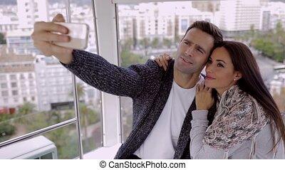 Loving couple taking a selfie in a ferris wheel gondola as...