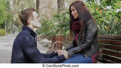 Young man kneeing down talking to his girlfriend