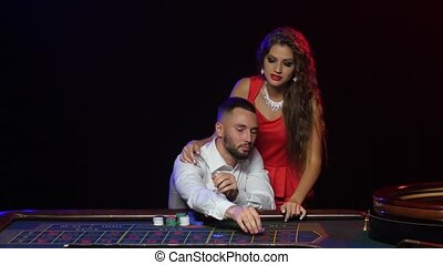 Man and beautiful girl in the casino wins in roulette