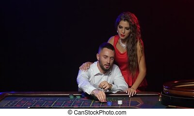 Croupier pushes a young couple to win at roulette chips -...