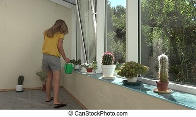 girl water cactus plants with watering can in greenhouse. 4K...