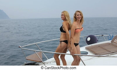 Two beautiful blondes in bikinis posing on yacht's bow in...