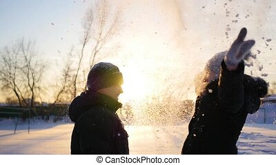 a guy and a girl throws snow above head and hugging on sunset background