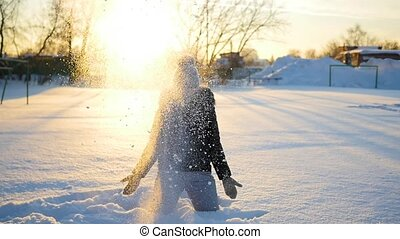 a girl throws snow above head on sunset background